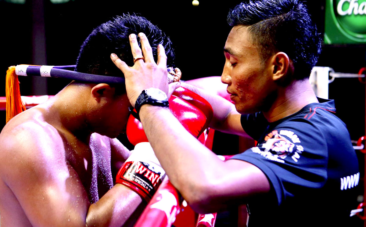 Kru Don performing the pre-fight prayer with the fighter wearing the Mongkong