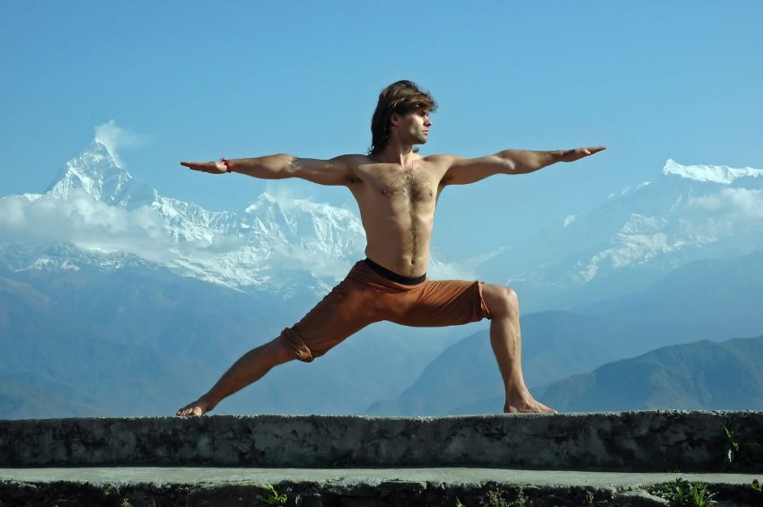 Man practicing yoga in Himalaya mountains, with view of Machapuchare, Nepal